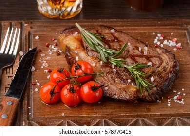 Delicious rosemary ribeye steak with cherry tomatoes, flatware on a wooden serving board, close-up. High-protein recipes.