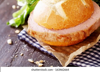 Delicious rustic lunch of a meat loaf sandwich with a crusty white rolled filled with a generous slice of German beef and pork loaf on a blue and white checkered napkin