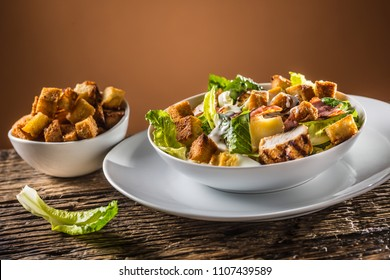 Delicious salad caesar with grilled chicken breast croutons eggs bacon parmesan cheese and  lettuce with dressing.