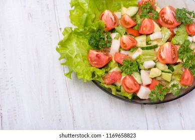 Delicious salad of fresh vegetables, turnips, cucumber, tomato, avocado and parsley on a white background