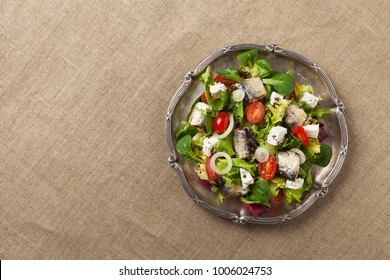 A delicious salad with sardines and feta cheese. Top view.