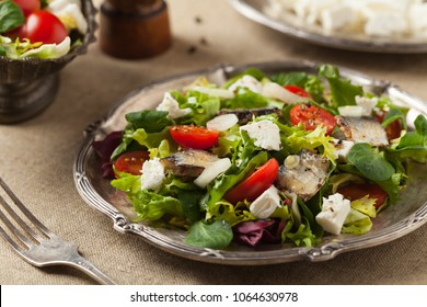 A delicious salad with sardines and feta cheese. Front view.