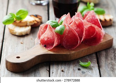 Delicious salami with basil and wine, selective focus