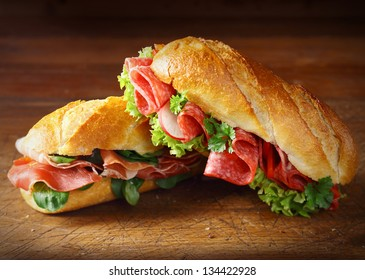 Delicious salami and ham baguettes with fresh lettuce and basil on an old wooden kitchen table top