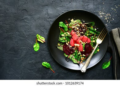 Delicious sald with chard leaves, beetroot and grapefruit slices on a black plate over dark slate or stone background.Top view.