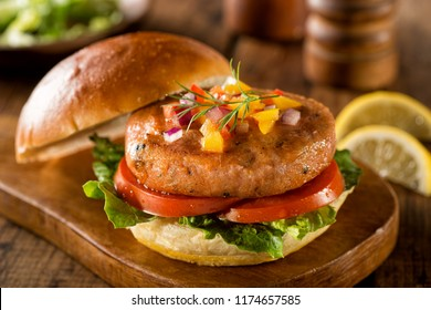 A delicious salmon burger with lettuce, tomato and pepper salsa with onion.
