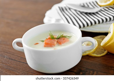 Delicious salmon cream soup in white bowl with lemon and striped cotton serviette on wooden table, close up