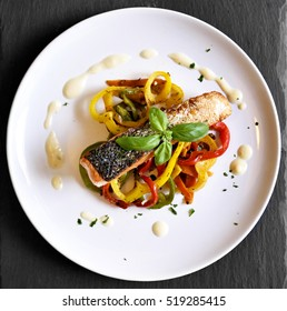 Delicious salmon filet and red bell pepper vegetables on a white plate. High angle shot of a healthy meal, decorated with basil leaf.