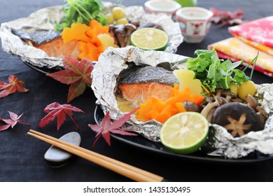 Delicious salmon fillets baked in foil with autumn leaves shaped vegetables and mushrooms