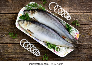 Delicious salted herring with onion on the old wooden background. Rustic style.