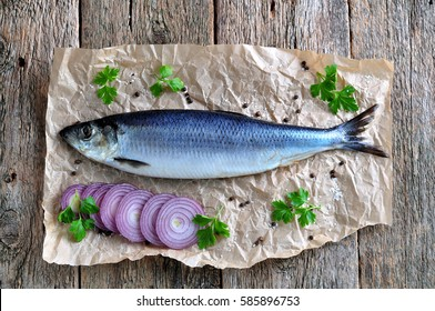 Delicious salted herring with red onion, salt and pepper on the old wooden background. Rustic style.