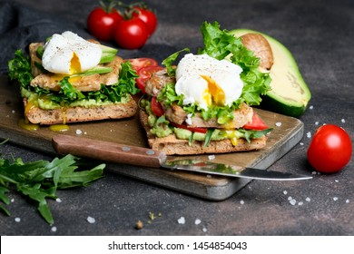 Delicious sandwich with avocado and poached egg on a dark background.