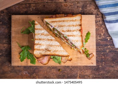 Delicious sandwich cut into triangles - toasted bread with chicken breast, fried bacon, tomatoes, onions, pickles with mustard and arugula salad close-up on a wooden board on a rustic table, top view