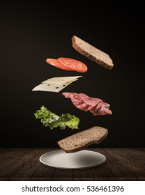 Delicious Sandwich with floating ingredients on the wood table black background