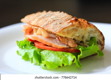 Delicious sandwich with lettuce leaf, tomato and ham on a white plate. Crusty bread, food for lunch.