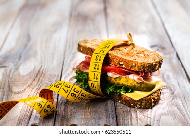 Delicious sandwich with measure tape on wooden table. Healthy eating or diet concept