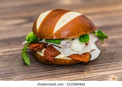 Delicious sandwich with meat and fresh vegetables on wooden background. Fresh baguette. Classic BLT sandwiches. Close up.