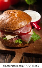 Delicious sandwich with prosciutto ham, cheese and vegetables on wooden background
