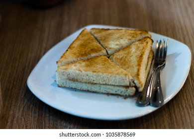 A delicious sandwich and silver forks on the white plate.