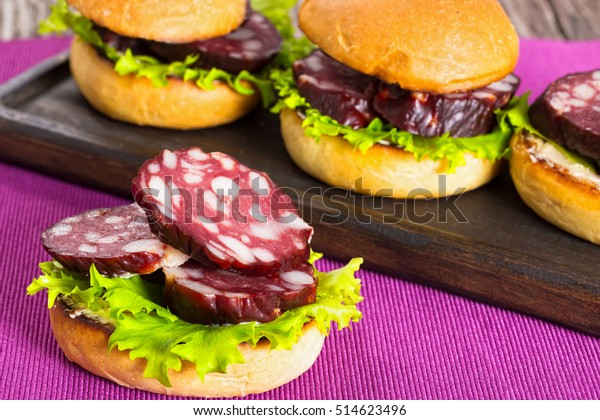 delicious sandwiches with butter, lettuce and slices of smoked sausage in fried bun on dark wooden board on table mat, close-up, view from above