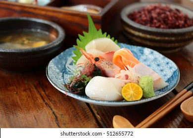 delicious sashimi on a japanese style bowl on top of wooden table, with rice soup and other dishes
