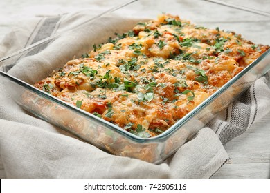 Delicious sausage casserole in baking dish on table
