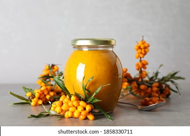 Delicious sea buckthorn jam and fresh berries on grey table
