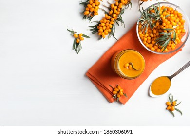 Delicious sea buckthorn jam and fresh berries on white wooden table, flat lay. Space for text