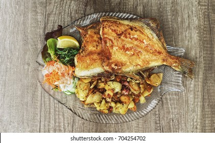 Delicious seafood dish - flounder, fried potatoes and salad