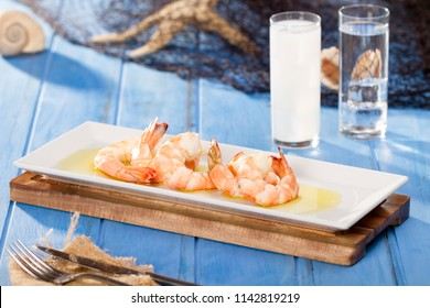 Delicious seafood Grilled Prawn at white plate with olive oil and raki or ouzo on bamboo cutting board serving with fishing net, shell, knife, fork and napkin on rustic blue wood table background.