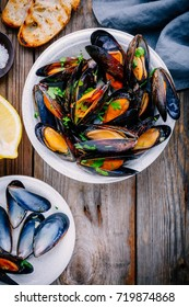 Delicious seafood mussels with with sauce and parsley.  Lemon and baguette . Clams in the shells.  Top view.