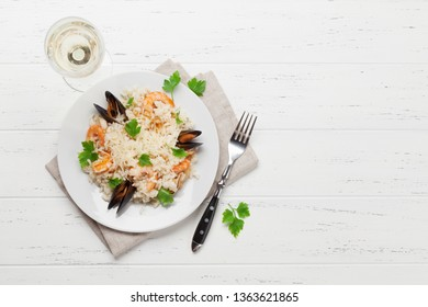 Delicious seafood risotto with shrimps, prawns, mussels. Dressed with parmesan cheese and parsley. Top view with white wine glass and copy space