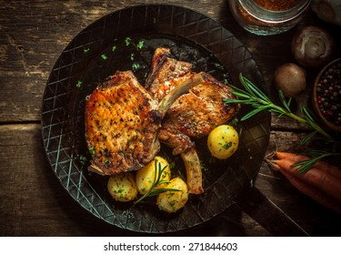Delicious seasoned pan fried pork cutlets cooked in a spicy marinade and served with boiled baby potatoes in their jackets garnished with rosemary , overhead view with ingredients