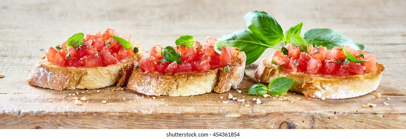 Delicious seasoned savory Italian tomato bruschetta slices on a rustic wooden board garnished with fresh basil leaves, horizontal banner