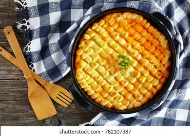 delicious shepherd's pie or cottage meat pie in baking dish on dark wooden table with kitchen towel and wooden spatulas , authentic recipe of english cuisine, horizontal view from above