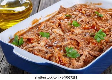 délicieuse viande de poulet râpée jetée dans une sauce barbecue, chargée de saveurs de chipotes fumés dans un plat de cuisson, sur vieille table en bois avec huile d'olive sur fond flou, en gros plan, macro