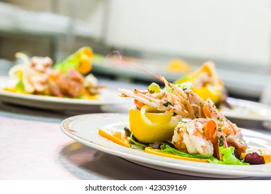 Delicious shrimp appetizer with colorful  fresh mediterranean fruits garnish on elegant white plates in restaurant kitchen