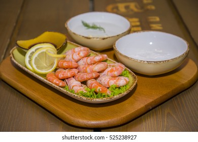 Delicious shrimp laid out on a plate with lettuce, sauce and a slice of lemon