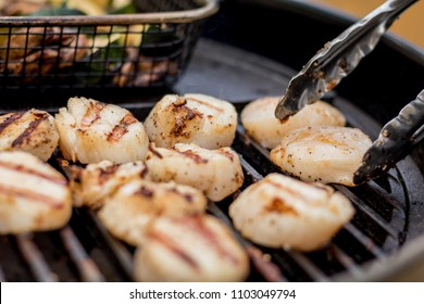 Delicious sizzling sea scallops grilling on a charcoal grill