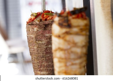 Delicious skewered fast food chicken and lamb mutton kebab, shawarma meat cooking and turning side by side on rotating spit Arab Middle Eastern or Mediterranean style.. Selective focus.