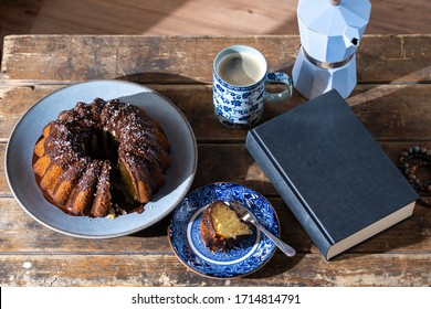 Delicious slice of Easter cake, good book and hot coffee on old, dark wooden table - nice afternoon during stay at home.