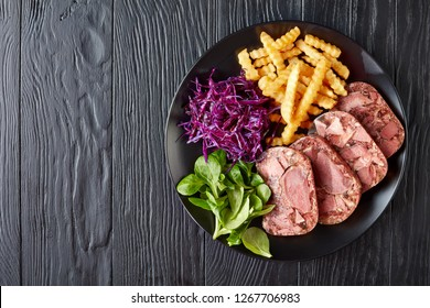 delicious sliced beef tongue and meat aspic served with french fries, green leaves and red cabbage salad on a black plate on a wooden table, view from above, flat lay, close-up
