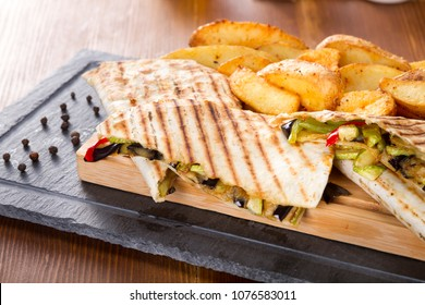 Delicious Sliced Mexican Quesadilla wrap with chicken, mushroom and sweet pepper, fried potatos and salsa serving on wood bamboo plate with black stone. Quesadilla is tortilla, usually corn tortilla.