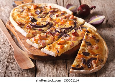 Delicious sliced pie flammkuchen with bacon and red onion close-up on the table. horizontal
