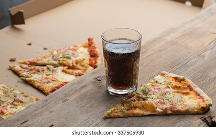 Delicious sliced salmon pizza and coke on a wooden table