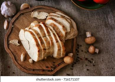 Delicious sliced turkey breast on wooden board
