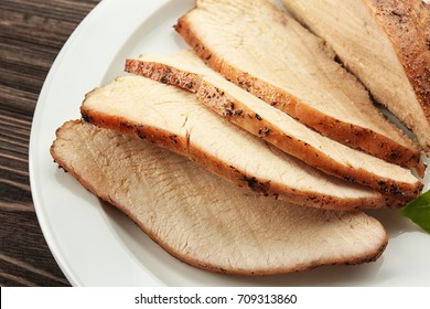 Delicious sliced turkey on white plate, closeup