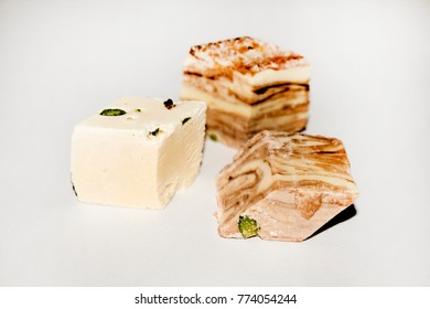 Delicious slices of Oriental milk cacao halva with the pistachios on the white background. Uzbek traditional handmade sweets. Tasty Asian organic delights. Healthy eco food.