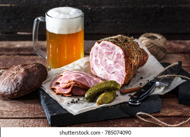 Delicious smoked ham on a blackwooden board with beer and pickles