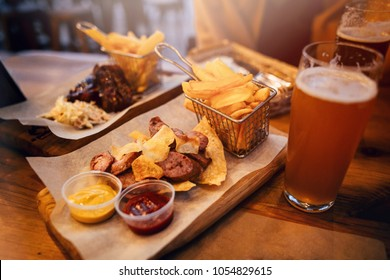 delicious smoked sausage with chips, french fries and steak with sauce on wooden  board. street fast food festivel concept. roasted meat and cold beer drinks.stylish  service